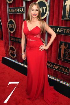 "Sofia Vergara redefines the role of ""lady in red"" in a one-shoulder gown with sheer, corseted detail at the waist by Donna Karan Atelier.   - HarpersBAZAAR.com"