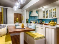 This+charming+blue+and+white+kitchen+features+a+wood+table+with+yellow+cushioned+banquette+seating.+The+white+kitchen+has+glass+front+cabinets+and+a+bright+blue+subway+tile+backsplash.
