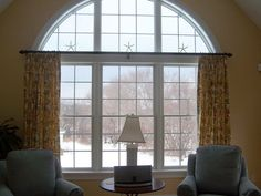 Option for arched window treatment, although this is different from yours. Need to make sure there is room for a bracket on either side. Keeping cornice board and hiding curtain rod inside is probably best option.