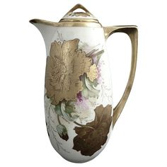 An antique porcelain chocolate pot featuring a transfer print with a heavy gold, hand painted design of poppies in full bloom. Each flower is