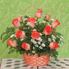 primaveral cesta de rosas naranjas adornada con aster, que son como pequeñas margaritas y verdes decorativos. Ideal para enviar a domicilio. #quedeflores.com #qdf #floristería #floresadomicilio #cestaderosas #rosasnaranjas #aster
