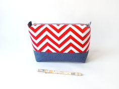 Zippered make-up/cosmetic pouch with red and white chevrons and a dark blue accent, with a light grey zip