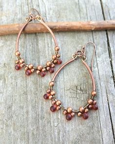 """Tiny red Czech glass teardrops wire wrapped with antiqued copper beads, finished with curved copper tubes. Very light weight, approx 2"""" in length."""