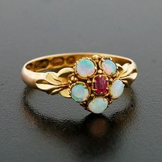 An absolutely lovely opal and amethyst ring from the Georgian (ca1850) era! This beautiful ring is made of 15kt yellow gold and displays a flower-like cluster at its center. Five cabochon opal petals surround an amethyst center, forming a wonderful, colorful flower.
