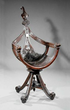 An Italian Carved Walnut Gondola Chair, late 19th c., probably Venetian, fiddle shaped finial centering griffin cartouche, molded arms terminating in lion masks, shaped splat with mask, curule seat with scrolled acanthus, scrolled legs, stretcher with lobed finial