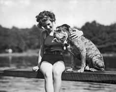 A young woman and her English bulldog relaxing on a diving board over a pond. 1928. Pinned by Judi Crowe.