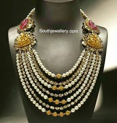 Brilliantly designed Rani haar with alternating strings of south sea pearls and polki diamonds hanging from the bottom of two Lakshmi side pendants on either side. Lakshmi pendants are studded with diamonds. Behind the Lakshmi pendants there are two carved ruby motifs on either side. Each south sea pearl string has Nakshi balls at its center