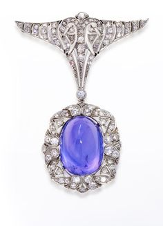 An art deco color-change sapphire and diamond brooch, circa 1925  the oval-shaped cabochon color-change sapphire within an openwork scrolling surround of old European-cut diamonds suspended from an openwork triangular-shaped panel of old mine, old European and single-cut diamonds; with fitted box signed Joseph Resch & Fils, Bucarest; sapphire weighing approximately: 40.70 carats; estimated total diamond weight: 1.50 carats; mounted in platinum; length: 2 1/4in.