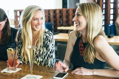 Smiling Caucasian women at bar with cocktails