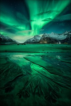 Spectacular reflections of the Aurora Borealis over the frozen waters of Flakstadya island in the Lofoten archipelago js