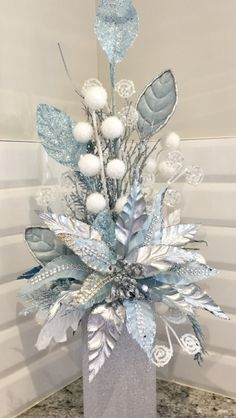 White silver and blue tall arrangement Christmas Vases, Christmas Flower Arrangements, Christmas Table Centerpieces, Christmas Swags, Christmas Flowers, Silver Christmas, Xmas Decorations, Christmas Home, Floral Arrangements