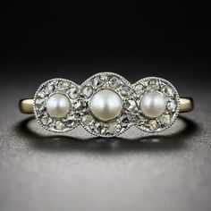 Antique French Pearl and Diamond Ring. Three small natural pearls are wrapped with twinkling rose cut diamonds in this petite and sweet antique ring. The platinum over 18 karat yellow gold ring, circa 1900