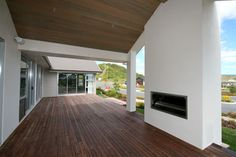 The outdoor fireplace with covered decking. The media room sits at the far end of the deck.