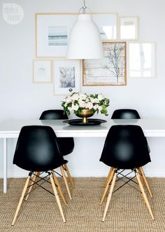 gallery wall with light wooden frames and white mounts in dining room with black chairs and white table, white walls, sisal rug