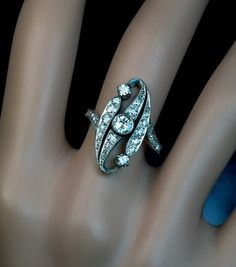 An Antique Belle Epoque Diamond Swirl Engagement Ring French with Russian import mark for 1899-1908 The platinum topped 18K gold ring is set with old Europ
