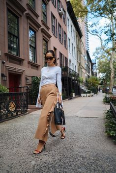 Aimee Song of the blog Song of Style shares an outfit post from New York Fashion Week, wearing MSGM ruffle pants and a knotted top.