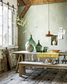 a dining space with wabi sabi aesthetics, a wooden dining set, concrete wlals and a rough wooden floor plus vases
