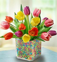 Tulips & Gems: 15 assorted tulips, unique double-walled vase, & bag of colorful beads. Fill outer wall of vase with decorative beads & the inner wall with fresh tulips. Easter Flower Arrangements, Easter Flowers, Flower Centerpieces, Spring Flowers, Floral Arrangements, Easter Centerpiece, Easter Colors, Easter Table Decorations, Easter Decor