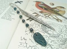 The body of this bookmark has a feather design which has been decorated with small glass beads with a metallic look and a small ceramic charm. Your bookmark will arrive tissue wrapped and placed in a. Feather Design, Organza Gift Bags, Bookmarks, Glass Beads, Metallic, Hair Accessories, Charmed, Pendant Necklace, Ceramics