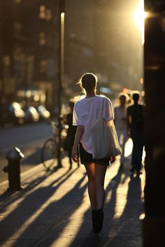 Great light - I'd prefer her facing us, walking toward photographer, and touching her face - easy shot to plan for (sunset and city corner), but also an easy shot to miss