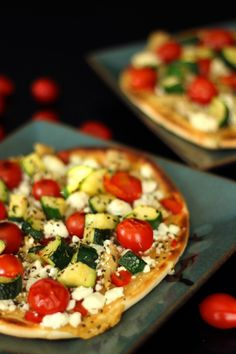 Mediterranean Flatbread Pizzas: Hummus for sauce, roasted red peppers, zucchini and cherry tomatoes topped with feta cheese and grilled. Yummy!