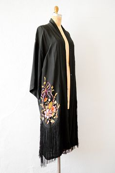 1920s silk flapper kimono robe with vibrant pink and orange flowers embroidered on the front and back. The hem has long black fringe. Snaps to close on front. Via Adored Vintage.