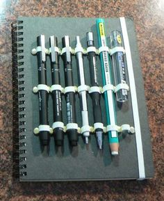 Make your own sketch journal with holders: You only need a notebook with heavy card stock covers, sewer's elastic, brass paper fasteners, and perhaps some super glue and duct tape.