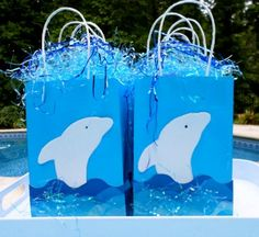 Dolphin party favors are found in these home made party bags. A wave bulletin border is used on the bottom of the party bag embellished with some extra sparkle of Easter grass.  Dolphin shapes are cut out of foam craft paper and glued to the bag.  Cute, easy and inexpensive. Click the picture for more dolphin pool party ideas.
