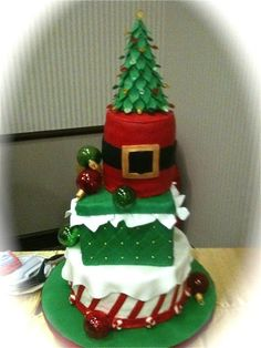"""12"""" round buttercream iced w fondant stripes & topped with fondant """"snow"""", 8"""" square fondant covered Christmas present box w fondant """"tissue hanging out"""", 6"""" round fondant Santa's belt tier, + hand made fondant Christmas-tree-cake topper with my hand poured sugar jewel ornaments; Christmas Ball Ornaments are hand my blown sugar """"glass""""; the little """"peppermints"""" are hand formed fondant; serves 172  (I will submit addt'l photos of close ups.)"""