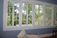 Wall of Marvin windows in living room.  Gorgeous view of the treetops and lakefront from this raised home.