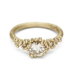 An alternative and unique solitaire diamond engagement ring with an antique cut champagne diamond in yellow gold handmade in Ruth Tomlinson's London studio.