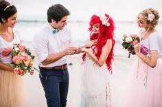 pareja casandose frente al mar mientras son acompañados por las damas de honor