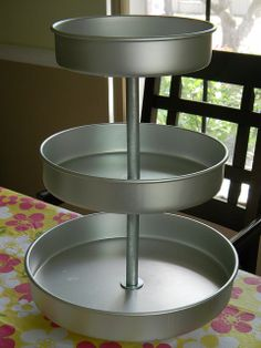With the help of a few pieces of pipe, some washers, and an ever trusty drill, this set of pans (which was purchased for around $20) was transformed into a tiered food display stand.