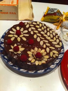 Homemade chocolate cherry almond torte, decorated with almond slivers and berries