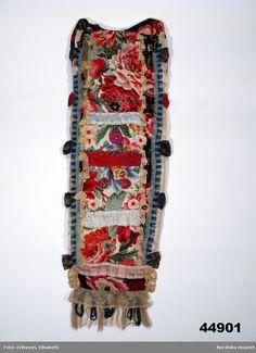 Doppåse, ovanligt lång med framstycke och del av bakstycket av storblommig tryckt yllemuslin i grälla färger.