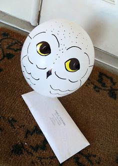 Purchase either helium-filled white latex balloons or blow up your own. Use sharpies to draw an owl face on each one (so that it resembles Hedwig) and then attach the balloon to your letter.