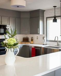 A builder grade kitchen gets a new look with classic features like gray cabinets, Quartz counters and subway tile. Remarkable!