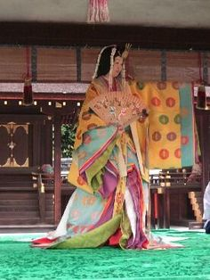 A woman dressed in junihitoe dancing for a kimono demonstration.