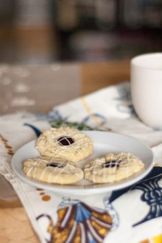 White Chocolate Raspberry Cookies. White chocolate thumbprint cookies with raspberry jam topped with a drizzle of more white chocolate. Elegant, delicious.