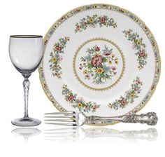 "Tableware set with ""Monroe"" glass pattern with gold trim from Lenox Crystal, ""Buttercup"" silver pattern from Gorham, and ""Ming Rose"" china pattern with gold rim, flowers, & scalloped edge from Coalport."