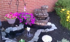 DIY pond. Paving rock, waterfall fountain, rocks, a few shovels, and plastic patio pond.