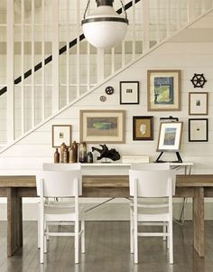 Coastal Modern by Tim Clarke Worn wood table, white chairs, nautical wall decor and art.