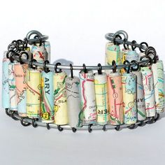 "This cuff style bracelet features hand rolled paper beads made from a vintage United States road atlas. The beads are on annealed steel wire strung on galvanized steel wire. This bracelet is 7 12""..."