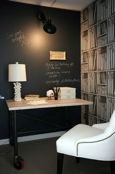 White & black sophisticated office design with black chalkboard accent wall, industrial reclaimed desk, white lamp, Restoration Hardware Martine white tufted chair with nailhead trim and faux library bookshelves wallpaper.