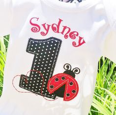 Appliqued Age in black with white polka dots with little Ladybug fluttering about! A red heart is trailing behind!