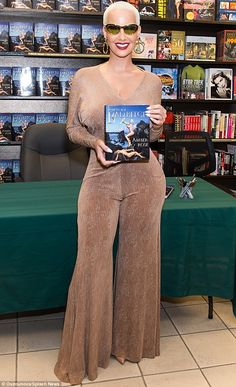 Worth a closer look: Amber Rose put on a busty display as she posed with her book in her h...
