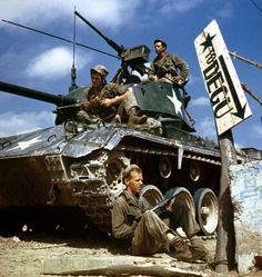 Crew of an M-24 tank along the Naktong River front. On the ground is Pfc. Rudolph Dotts Egg Harbor City N.J. gunner (center); Pvt. Maynard Linaweaver Lundsburg Kansas cannoneer; and on top is Pfc. Hugh Goodwin Decature Miss. tank commander. All are members of the 24th Reconnaissance 24th Division. (Army KOREAN WAR)