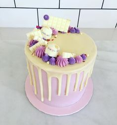 Red velvet cake with pink frosting, white chocolate drip and purple embelishments
