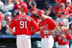 Jeremy Hazelbaker #91 of the St Louis Cardinals is congratulated by Greg Garcia #35 after hitting a two-run home run against the Boston Red Sox during the ninth inning of a spring training game at Roger Dean Stadium on March 21, 2016 in Jupiter, Florida. The Red Sox defeated the Cardinals 4-3.