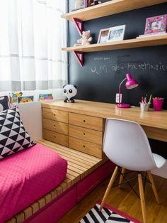 chambre de 9m2 pour enfant avec tableau noir pour écrire, lit sur plate forme, des tiroirs en bois sur la plate forme, chaise en plastique blanche sans accoudoirs, avec des pieds en bois clair